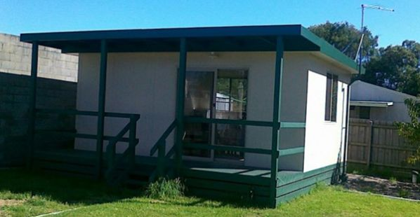 single room sleepout or bungalow with green verandah and white walls