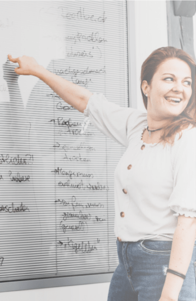 Woman smiling and showing on a whiteboard