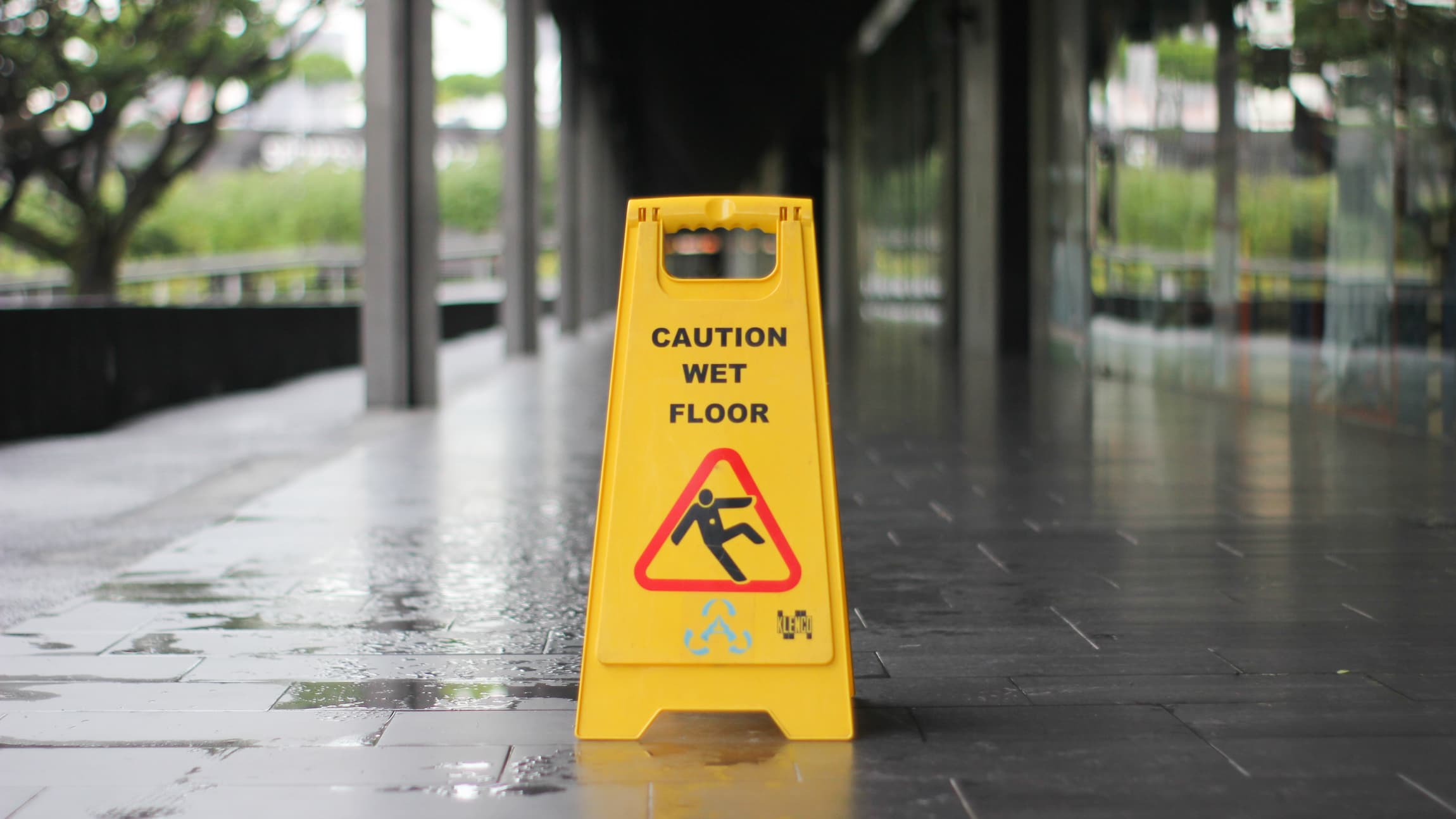 A yellow caution wet floor sign outside on a wet sidewalk.