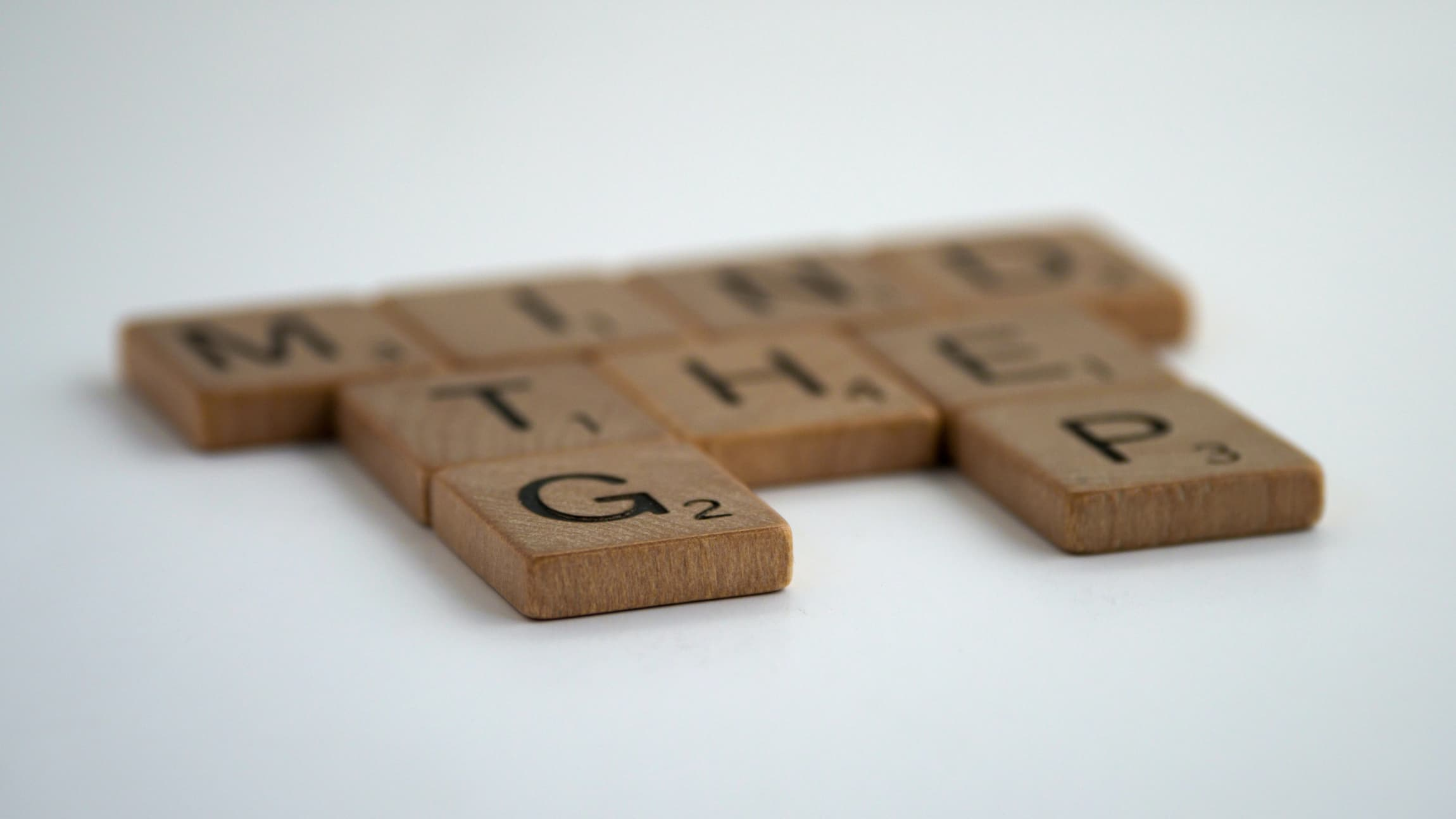 Wooden Scrabble game tiles arranged to spell mind the gap.