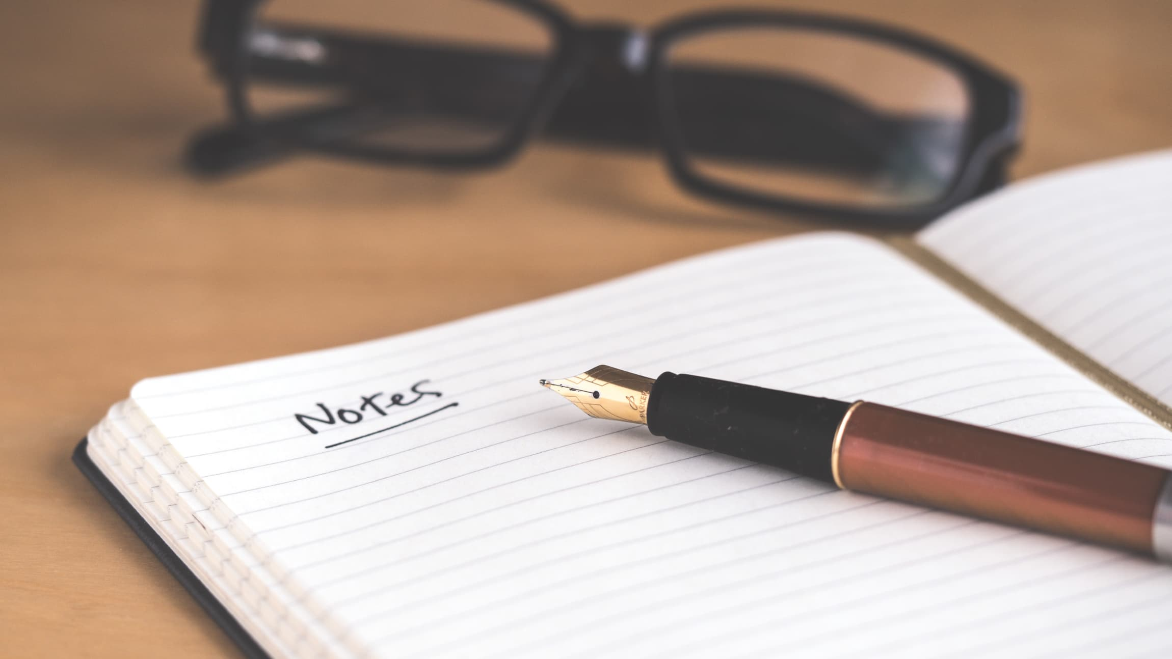 """A notebook lies open on a desk with the word """"Notes"""" written in it."""