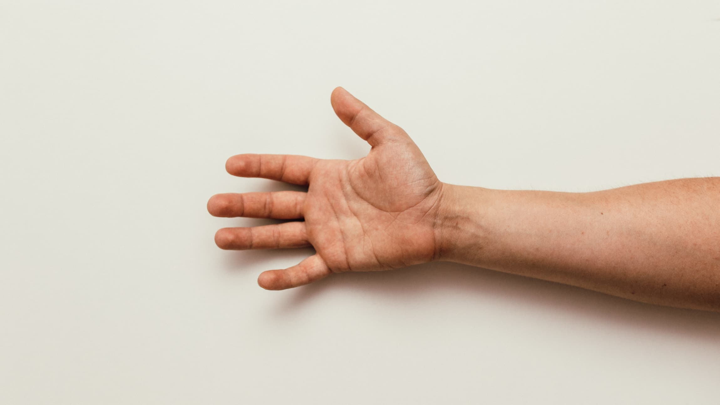 An open hand reaches into frame from the right side.