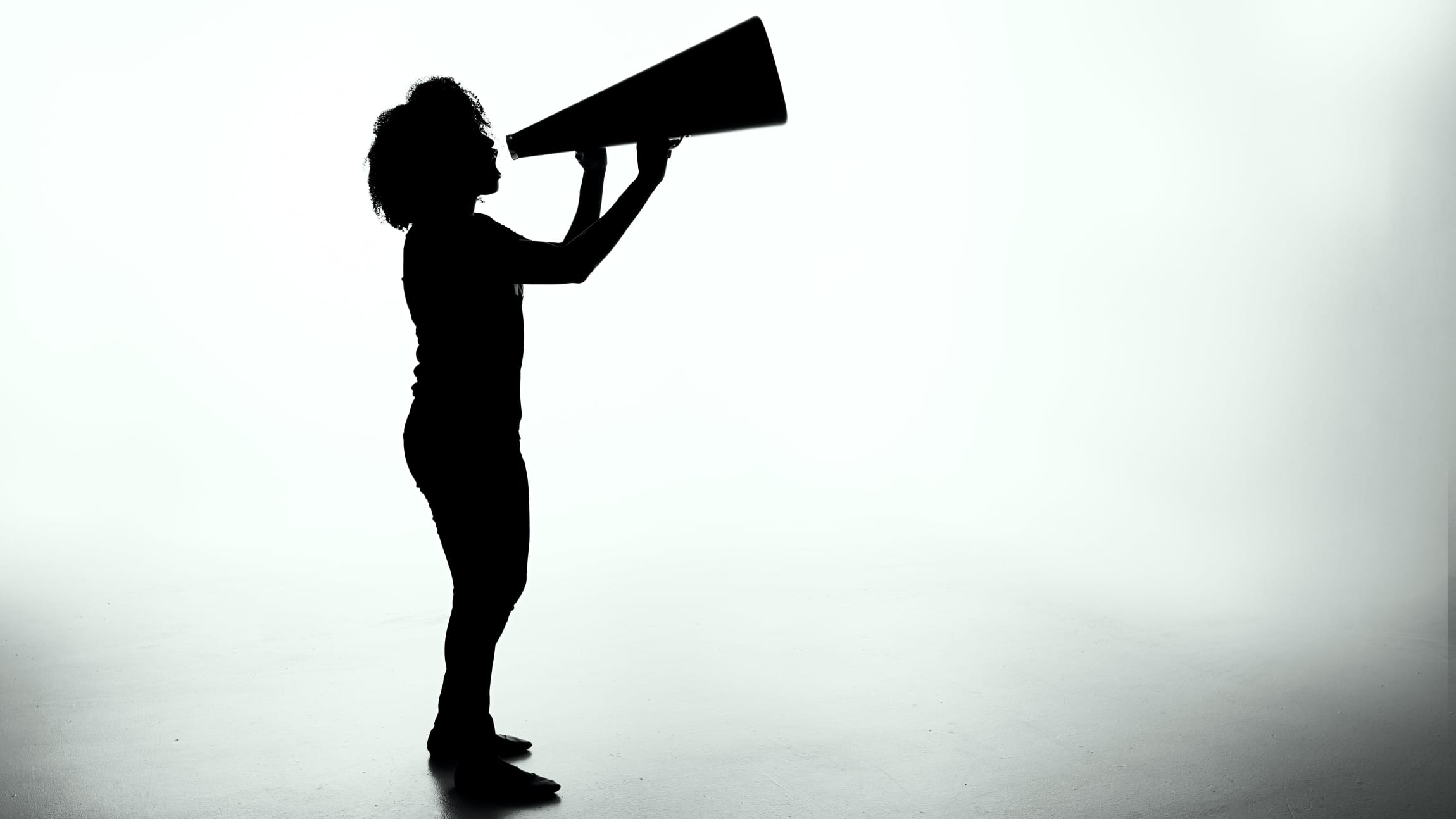 Silhouette of a person yelling into a megaphone.