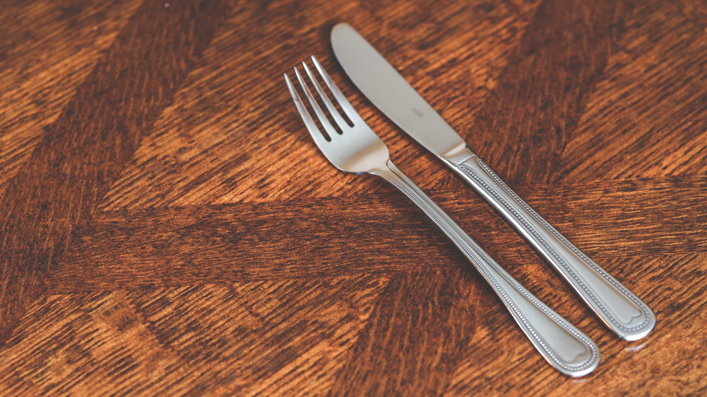 Fork and butter knife lying on a wooden table.