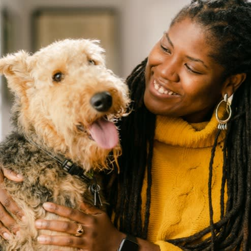 an employee with her dog smiling at the camera