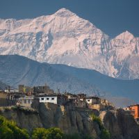 A small cliff town in front of the Himalayas in Nepal