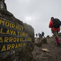 A sign on Mt. Kilimanjaro and hikers