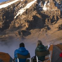 Hikers take a break to admire the views of Mt. Kilimanjaro.
