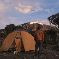 A tent and a hiker in orange admiring the view of Mt. Kilimanjaro.