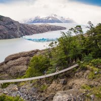 Hikers cross a foot bridge close to one of Patagonia's many glaciers.