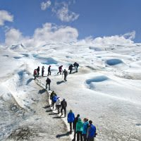Hikers ascend a snowy path up a glacier in Patagonia.