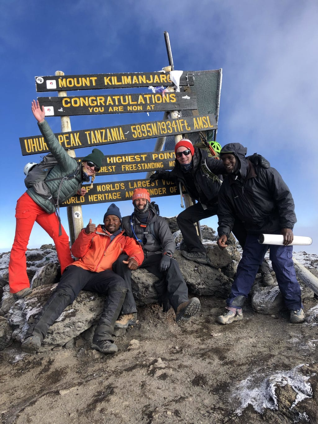 Summit of Mt. Kilimanjaro sign with five people