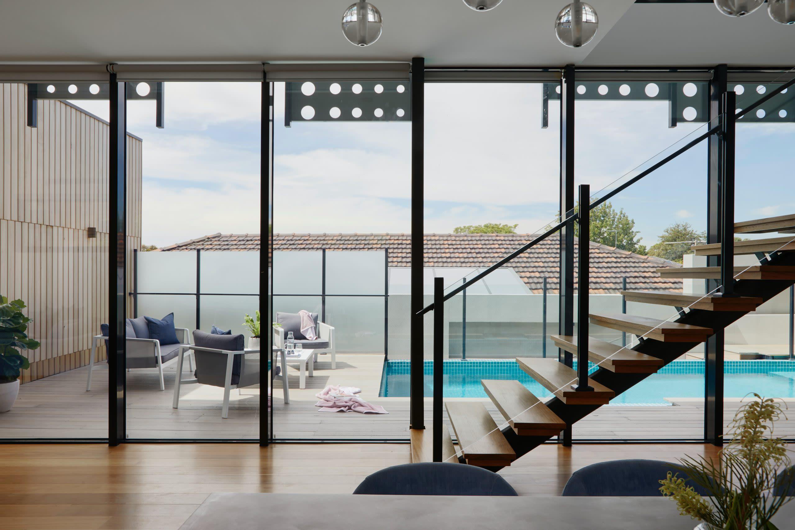 Fotografia do interior de um imóvel. À esquerda, é possível observar uma escada; ao centro, uma porta de vidro; e, ao fundo, uma piscina.