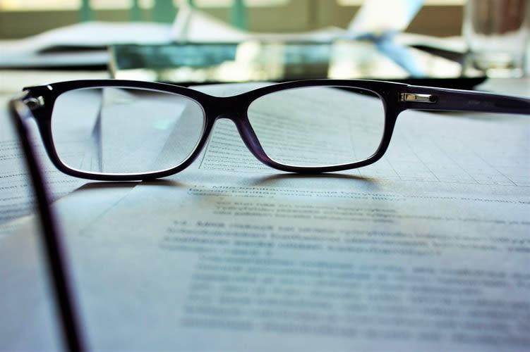a imagem mostra um documento desfocado, com um óculos em cima..
