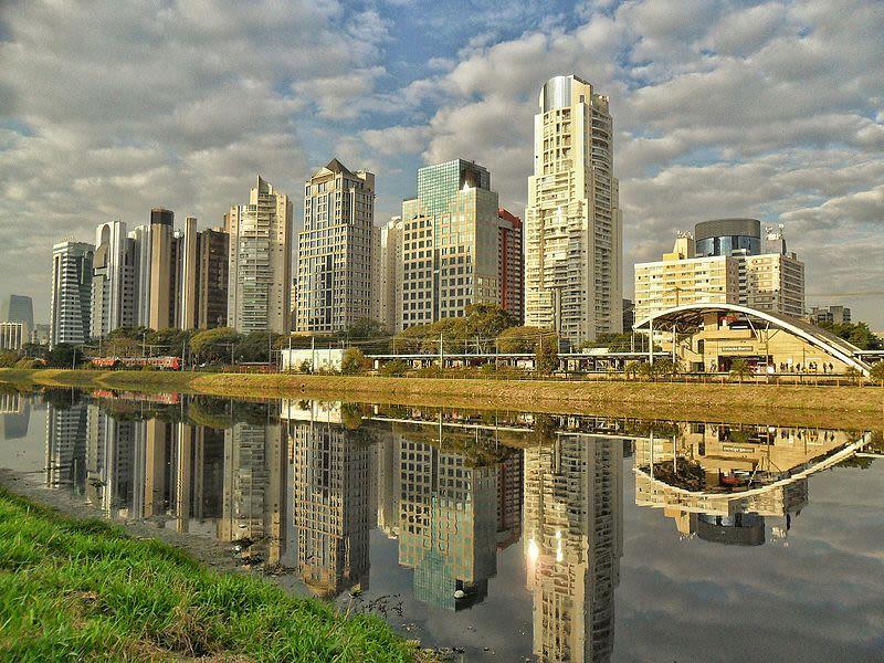 Foto da Marginal Pinheiro, em São Paulo com espelhos d´água. A imagem mostra um bairro cheio de prédios e uma estação de trem, reluzida em um rio.