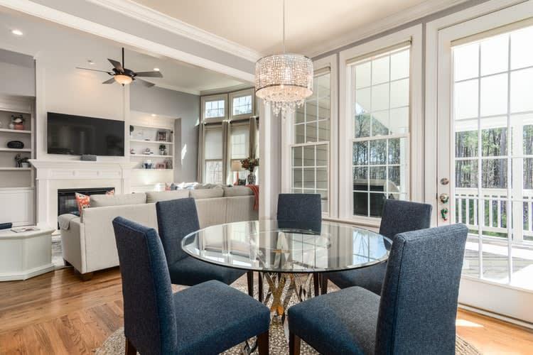 Como vender seu imóvel mais rápido com maior retorno. Na imagem, é observada uma cozinha integrada com uma sala de televisão. É possível observar poltronas azuis, uma mesa de vidro, portas de vidro, um sofá e uma televisão.