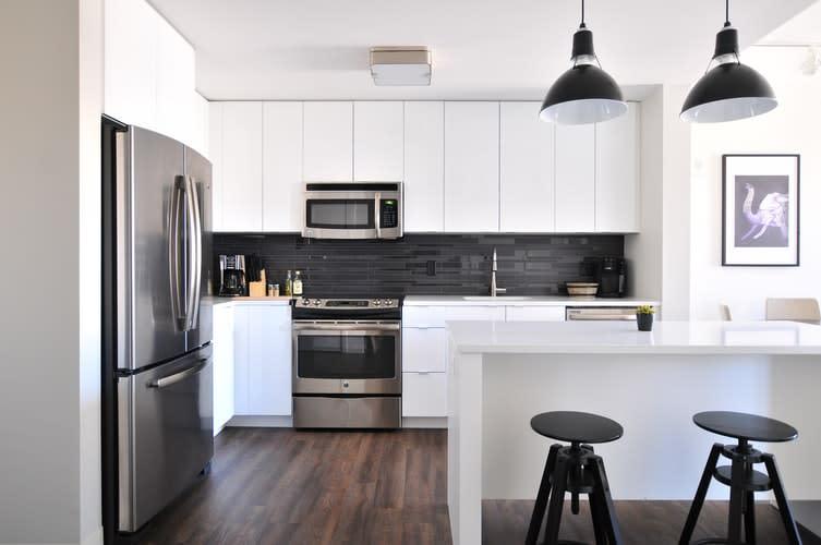 Faça fotos profissionais para otimizar o anúncio do seu imóvel. Na imagem, observamos uma cozinha de estilo americano com duas bancadas brancas, bancos pretos, uma geladeira em aço inox e um armário de parede branco.