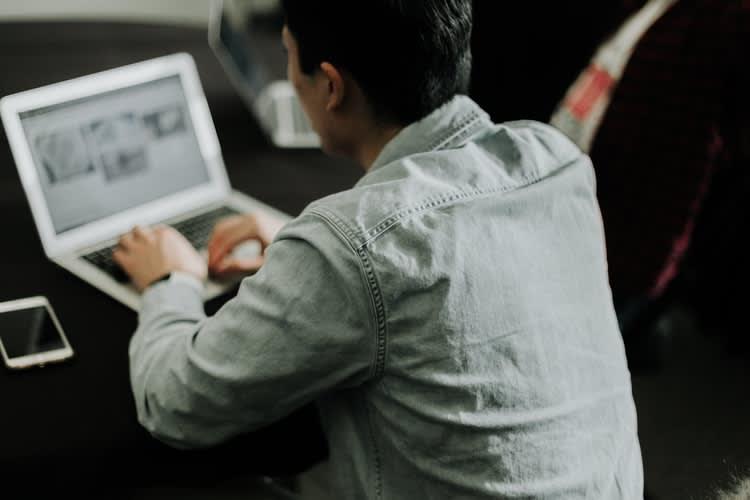 Na imagem é possível observar um homem de costas para câmera trabalhando em um notebook , editando a planta de um imóvel.