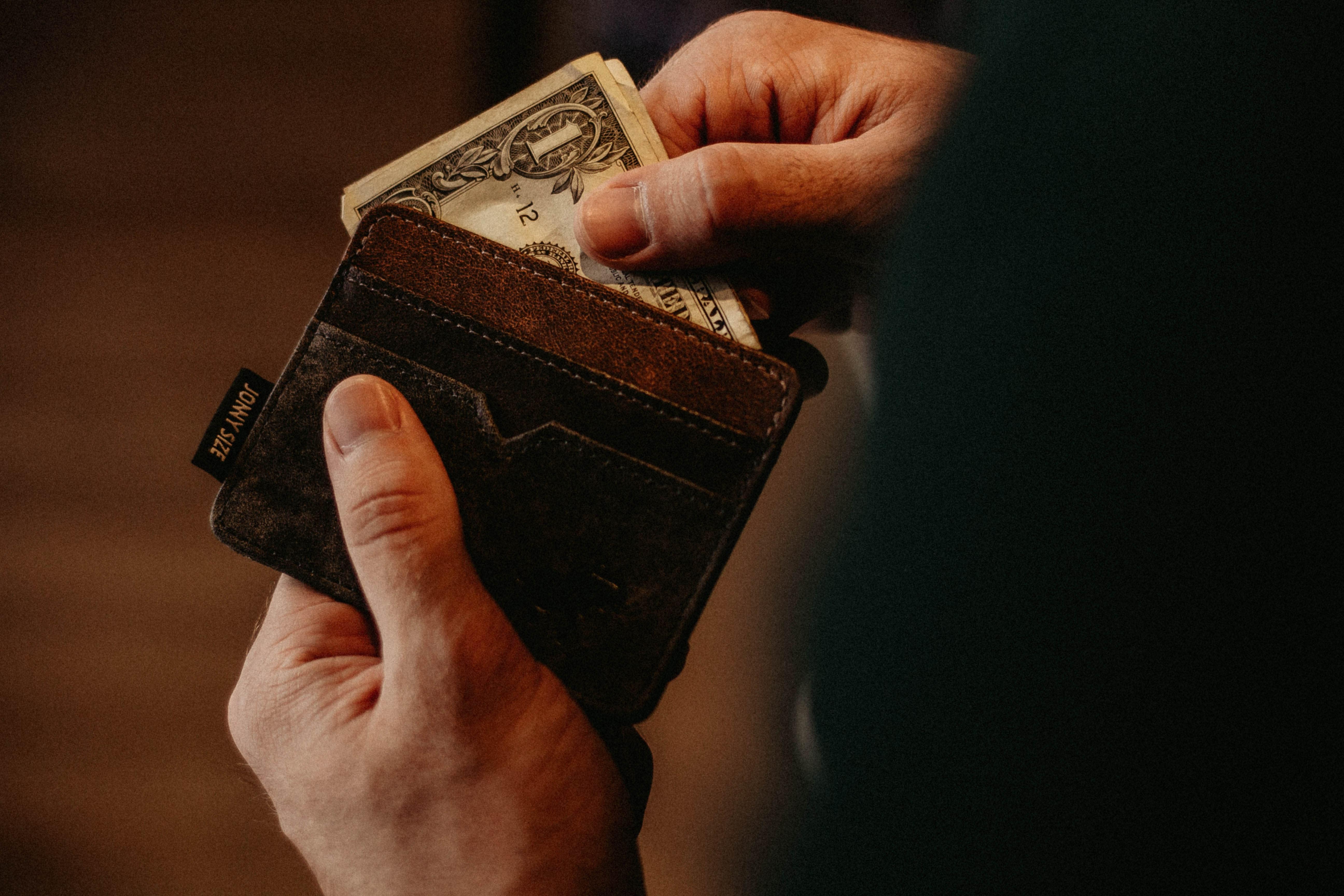 A imagem mostra uma carteira de couro marrom com uma nota sendo puxada pelas mãos de um homem, ilustrando o tema do texto