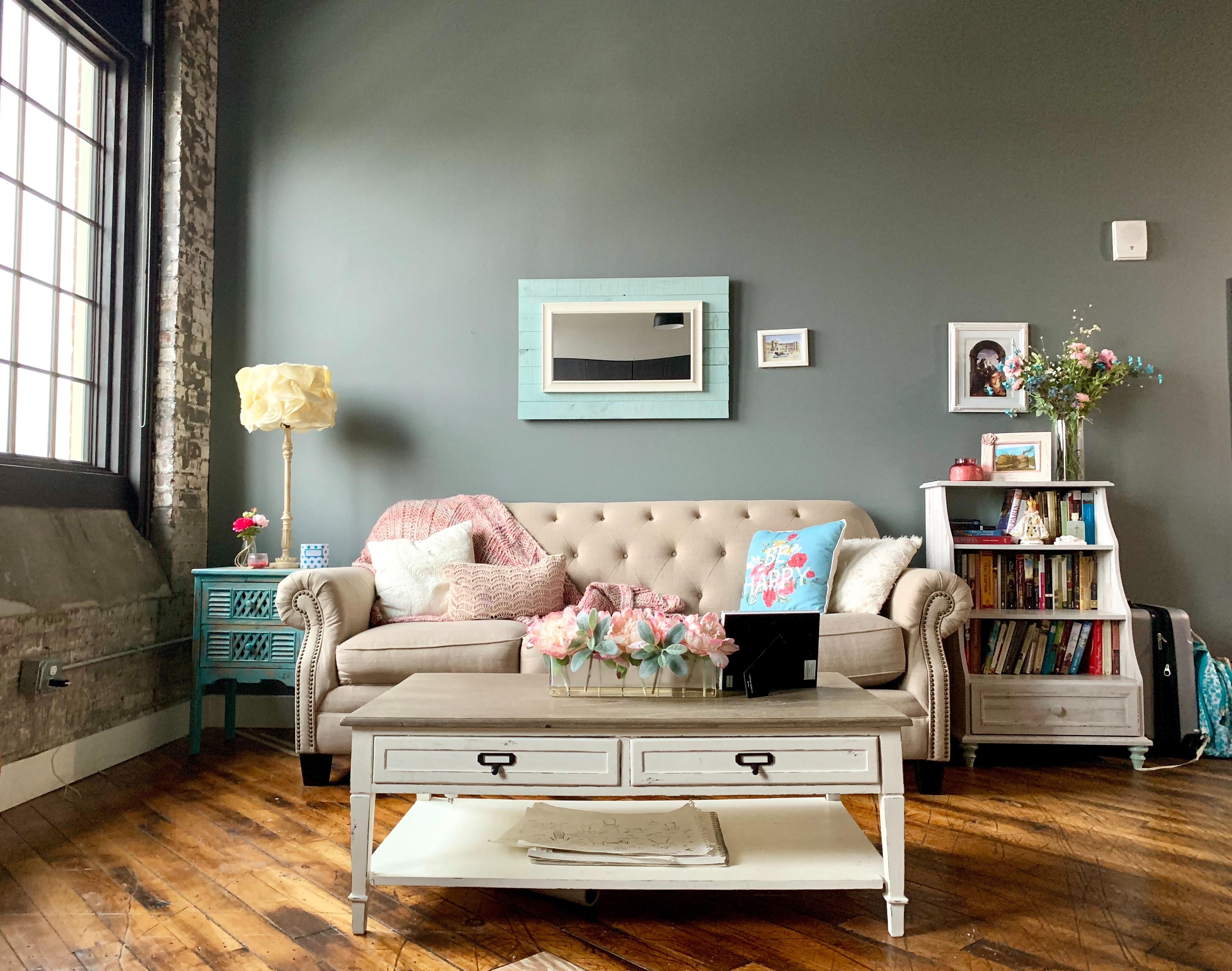 sala com sofá rosa centralizado e mesa de centro branca com detalhes em marfim