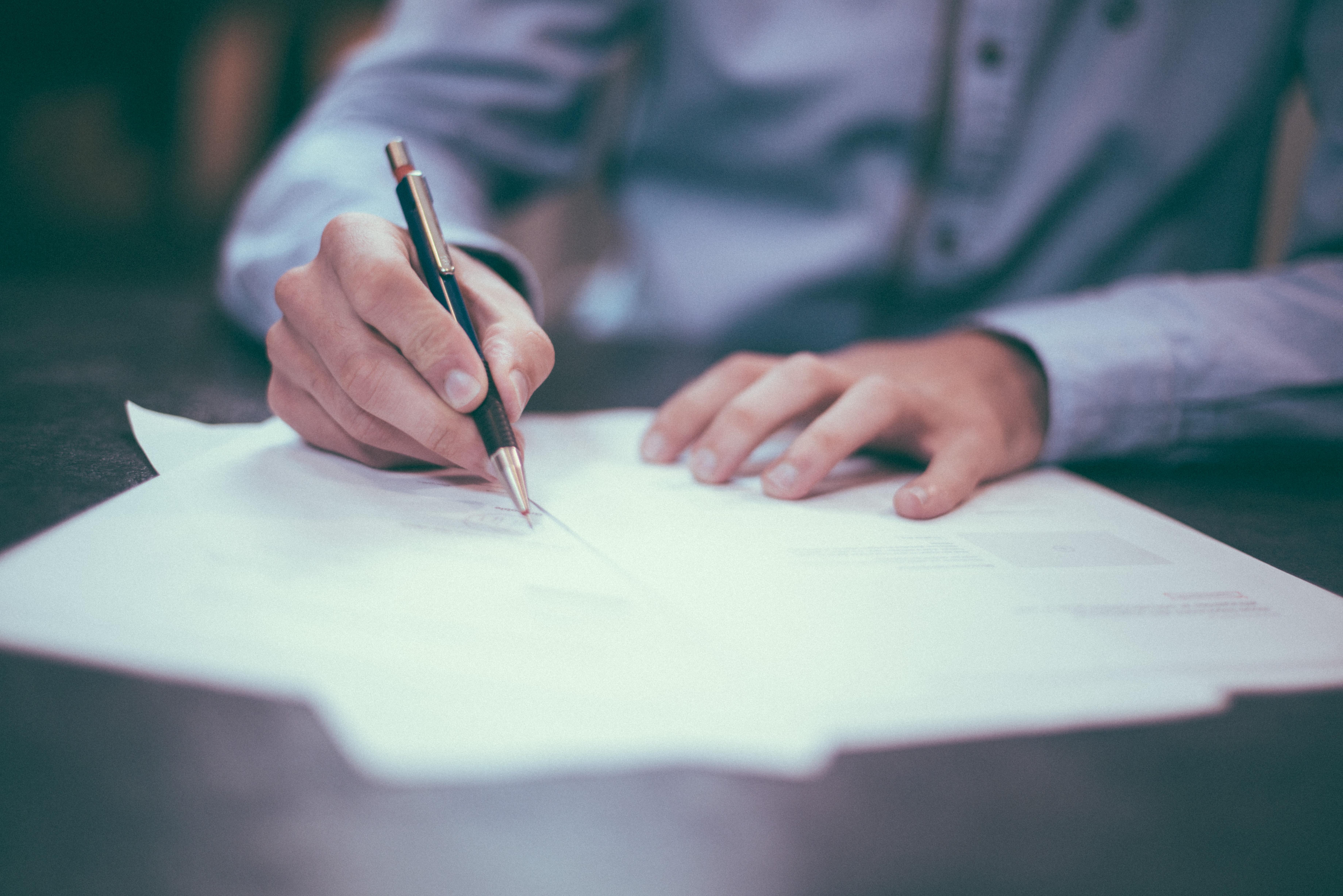 a imagem mostra uma mesa marrom com algumas folhas acima, representando contratos, e um homem vestido de camisa social azul clara assinando as imagens