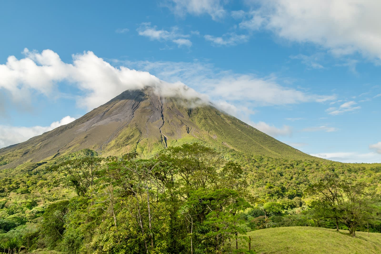 The Arenal volcano surrounded by clouds. This is an active volcano in tropical Costa Rica. The volcano slopes are covered in primary forest full of wildlife.