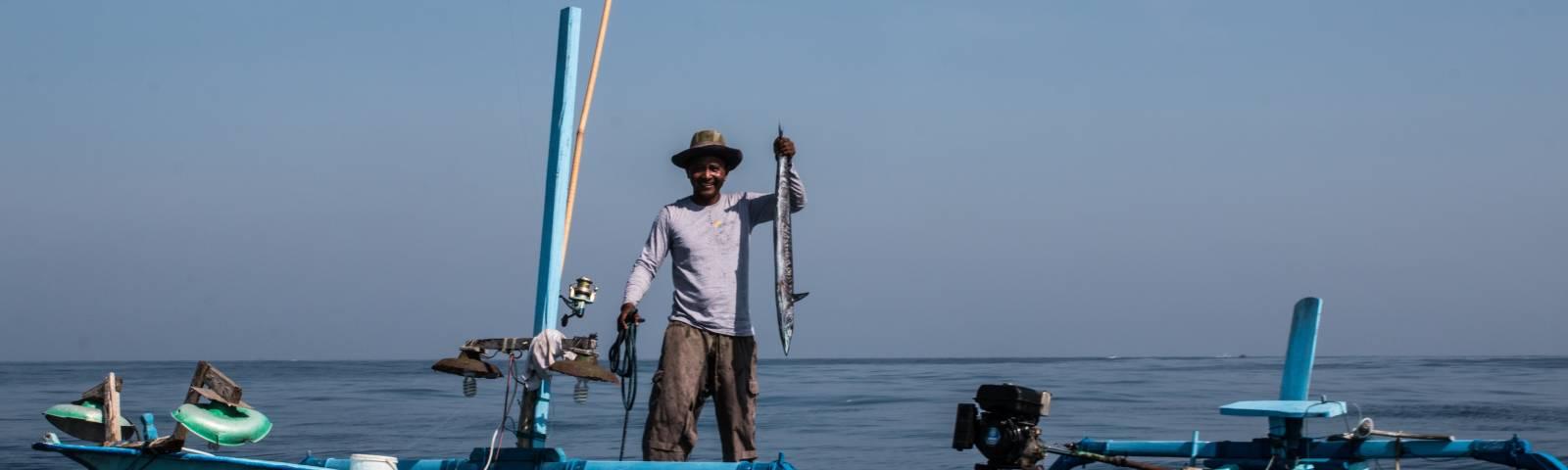 Fischer mit gefangenem Fisch auf einem Fischerboot namens Bali Indah auf Bali