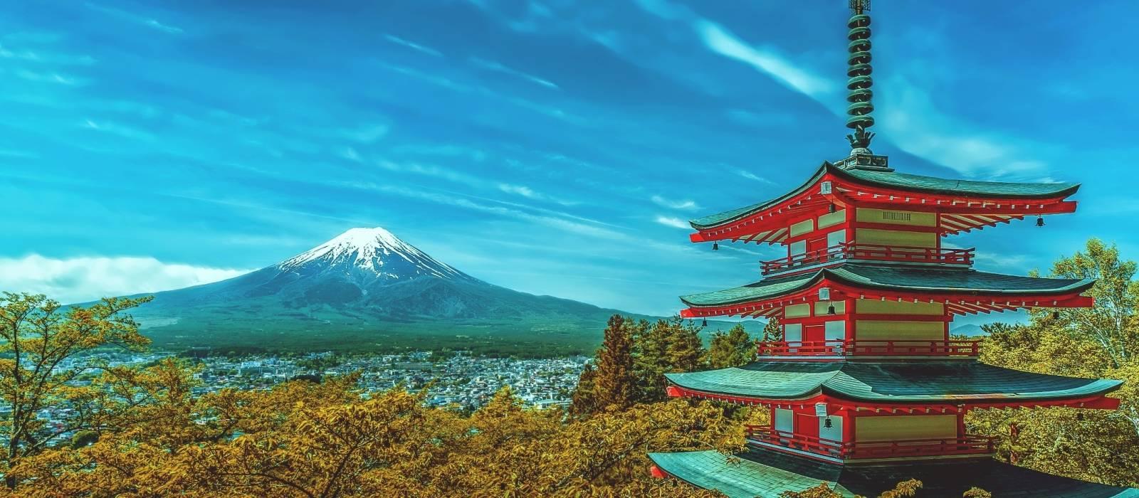 Blick auf den Mount Fuji hinter grüner Landschaft und einem japanischen Tempel in Japan