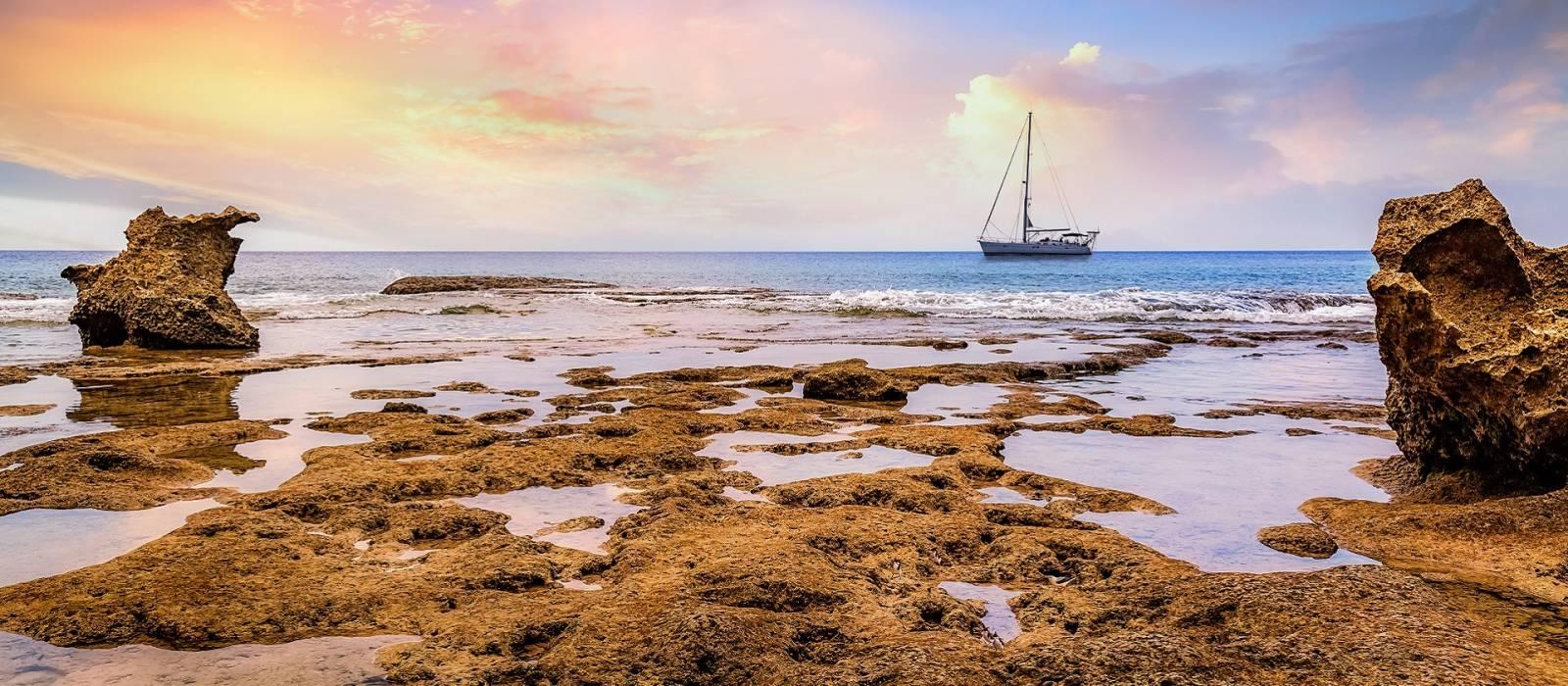 Beach sunset at Neil island Andaman India with naturals rocks and corals and sailing vessel at the horizon