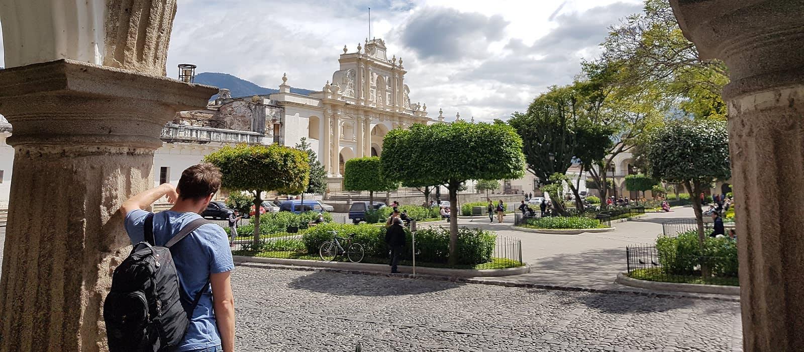 Is Guatemala safe: Enchanting Travels Guatemala Tour Traveller visiting market square in antigua, guatemala, looking at historical buildings