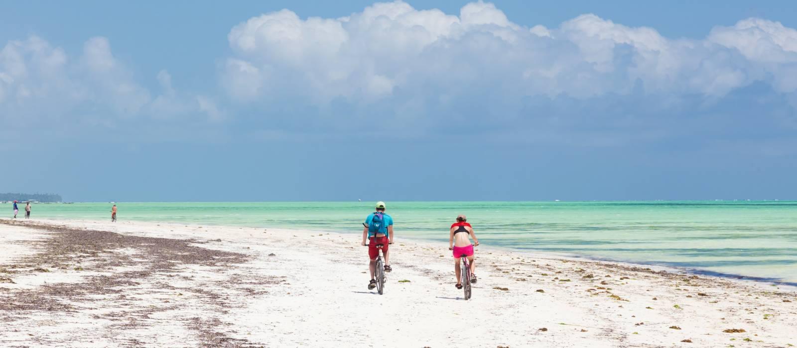 Tourist couple cycling down picture perfect white sand tropical beach of Paje village, Zanzibar, Tanzania, Africa