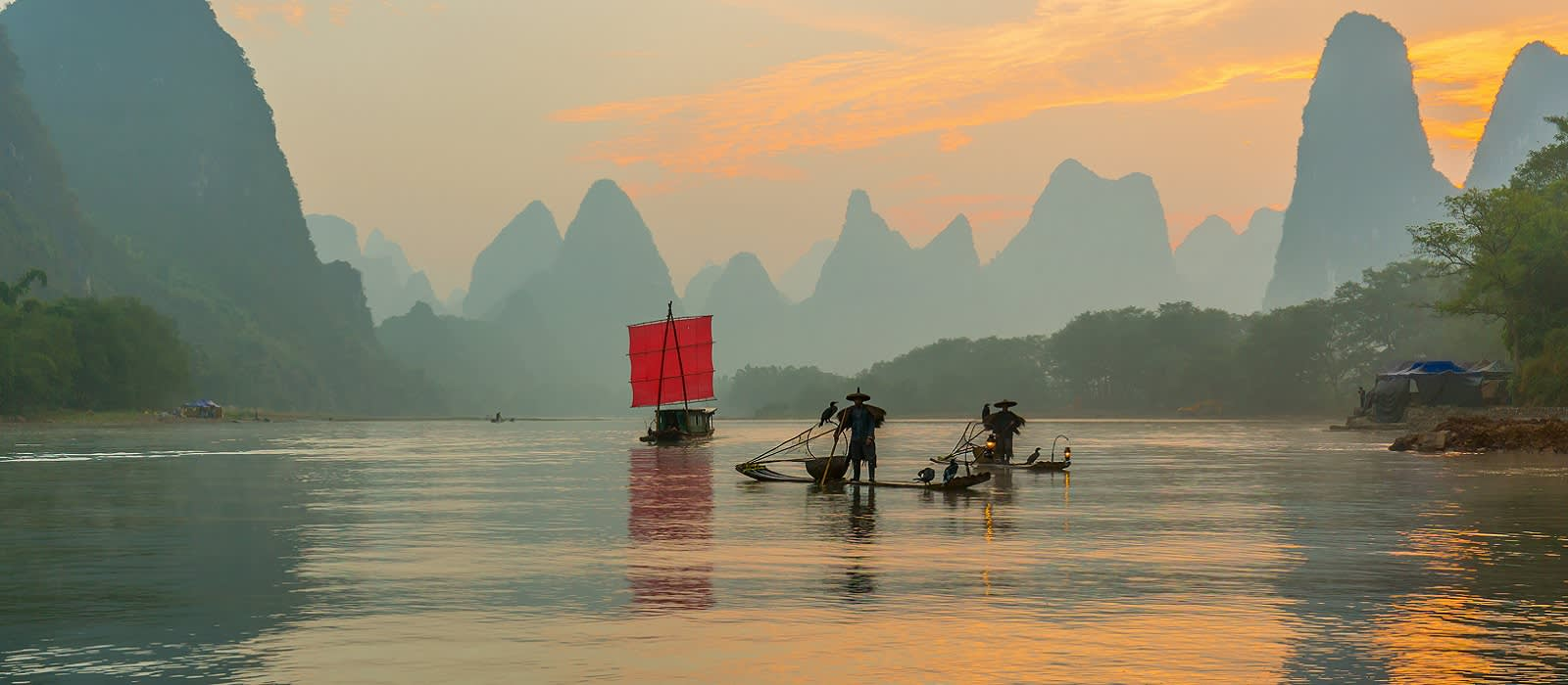 Enchanting Travels China Tours Fisherman stands on traditional bamboo boats at sunrise (boat with a red sail in the background) things to do in China