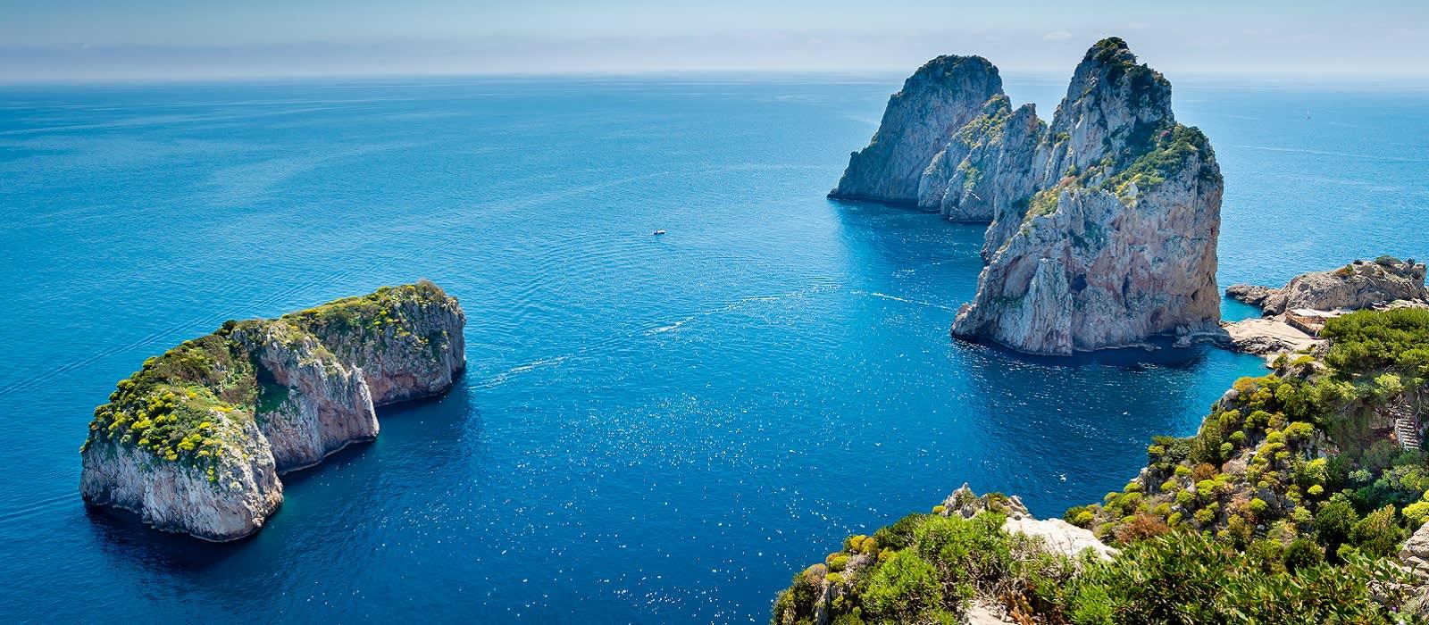 Enchanting Travels Italy Tours Faraglioni rocks view from hiking pass along Capri coastline , Italy.