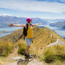 Enchanting Travels New Zealand Tours Woman Traveler with Backpack hiking in Mountains.