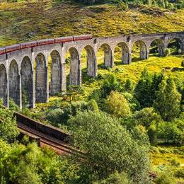 Enchanting Travels UK & Ireland Tours Glenfinnan Railway Viaduct in Scotland with the Jacobite steam train passing over