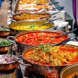 Enchanting Travels UK & Ireland Tours Variety of cooked curries on display at Camden Market in London
