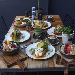 Gedeckter Frühstückstisch mit Tassen Kaffee und verschiedenen australischen Frühstücksgerichten im Melbourne Cafe, Australien