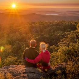 Paar sitzt am Felsrand und blickt in die Natur von Mount Kaputar in New South Wales, Australien