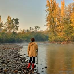 Wanderin mit Gummistiefeln steht am Tumut-Fluss in New South Wales, Australien