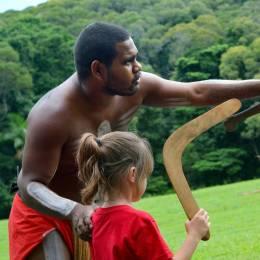 Yirrganydji-Aborigine mit Körperbemalung erklärt kleinem Mädchen die Bedienung eines Boomerangs in Queensland, Australien