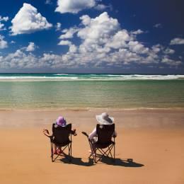 Zwei Camper sitzen in Campingstühlen am Strand