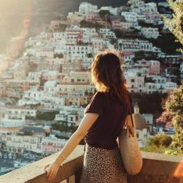 Young woman admiring panoramic view of Positano at sunset, Amalfi coast, Italy