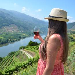 Girl with a glass of wine looking to the vineyards in Douro Valley, Portugal