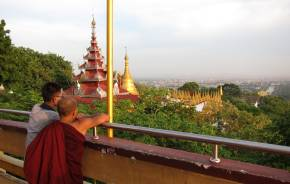 Ein junger Mönch und ein Junge in Myanmar genießen die Aussicht vom Mandalay Berg auf die Stadt und die goldene Pagode im Hintergrund