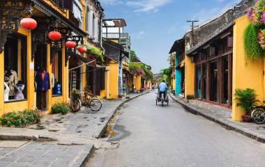 Radfahrer fährt vorbei an orangefarbenen Häusern in der Altstadt von Hoi An in Vietnam