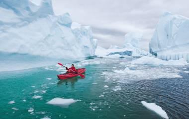 Man paddling on kayak between ice in Antractica, near Pleneau Island