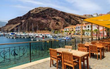 Chairs and tables of local restaurant in harbour with boats and yachts and colorful houses, Madeira island, Portugal