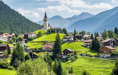 Graubuenden, Switzerland with view of houses on green grassy hills