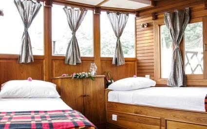 Holzvertäfelte Kabine der Amara Cruise mit zwei Betten und Gardinen in Myanmar