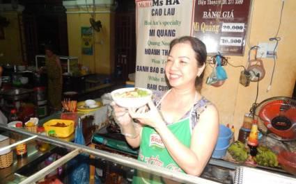 Köchin hält eine Schüssel mit Nudelsuppe hoch, Vietnam